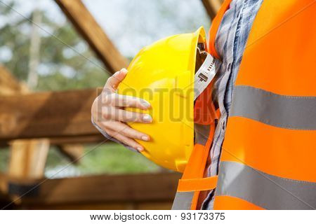 Midsection of female construction worker holding yellow hardhat at site
