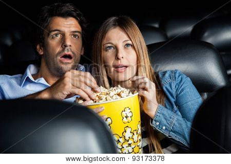 Shocked mid adult couple having popcorn while watching movie in cinema theater