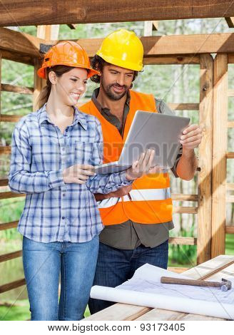 Male and female architects using laptop together at construction site