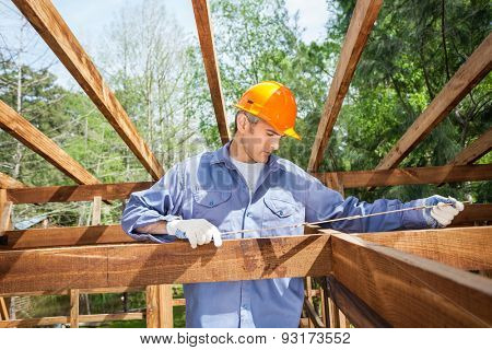 Male construction worker measuring timber frame with tape at site