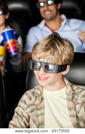 Happy boy watching 3D movie with family in background at cinema theater