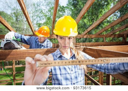 Confident architect using measure tape while construction worker working in background at site