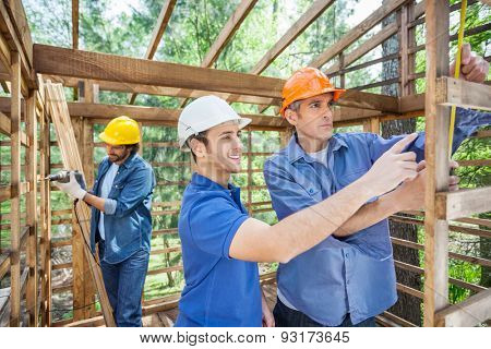 Male workers working in incomplete timber cabin at construction site
