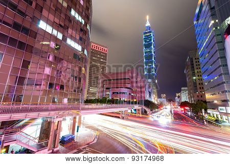 Busy traffic light trails in modern street and illuminated landmark of taipei at night