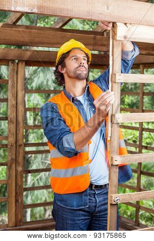 Mid adult male worker measuring timber frame with tape at construction site