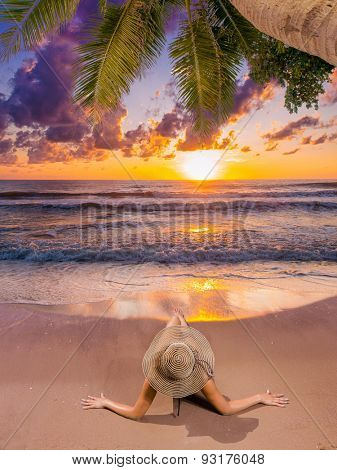 Young woman watching as sun sets over Bali Indonesia