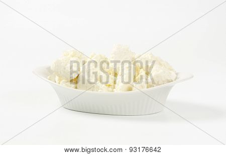 slices of fresh curd cheese in white oval bowl