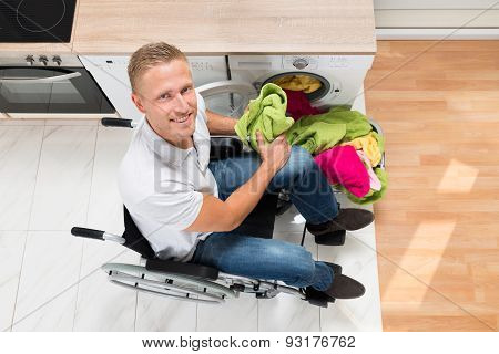 Man On Wheelchair With Clothes In Kitchen Room