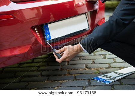 Man Changing Car's Number Plate
