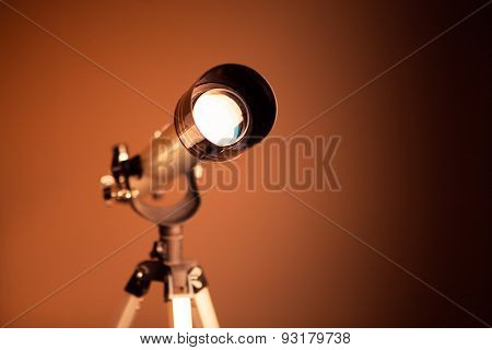 telescope on brown background with copy-space