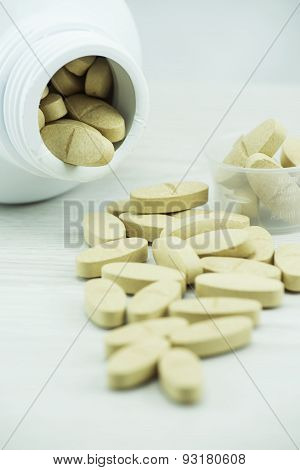 Brown pills an pill bottle on the table.