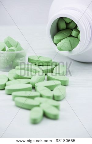 Green pills an pill bottle on the table.