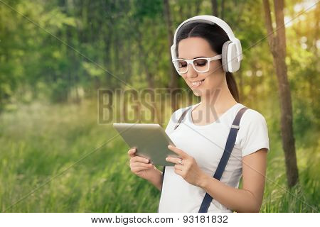 Girl with Headphones Listening to Music and Holding a Tablet PC