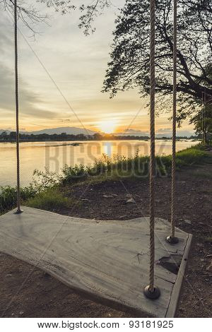 lone swing at river side and sunset ,Thailand . Vintage Tone.