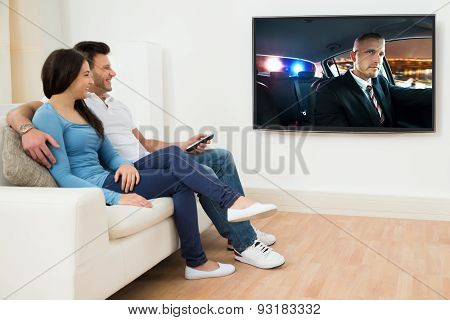 Happy Couple In Livingroom Watching Movie