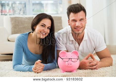 Happy Couple With Piggybank Lying On Rug