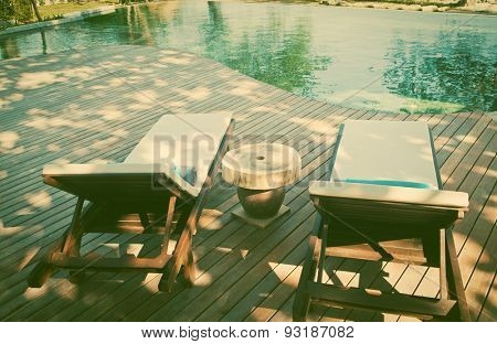 Sunbeds with towels near swimming pool - retro style photo