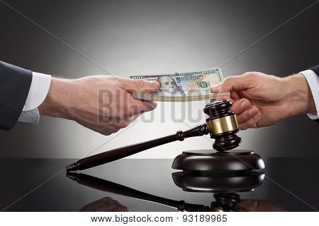 Businessman Taking Bribe In Front Of Mallet