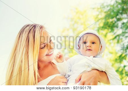 family, child and parenthood concept - happy mother with little baby in park