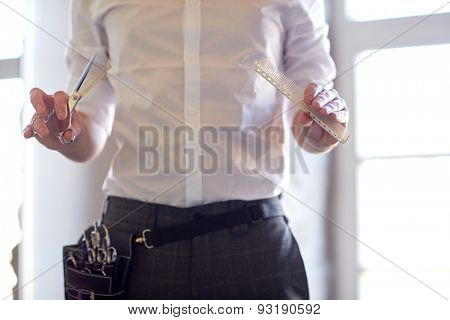 beauty, hairstyle and people concept - close up of male stylist with scissors and comb at salon