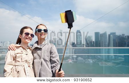 people, children, friends and technology concept - happy girls taking picture with smartphone on selfie stick over in singapore city background