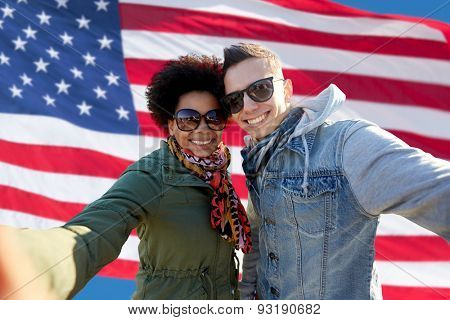 people, international friendship and technology concept - happy international teenage couple taking selfie over american flag background