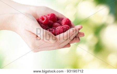 healthy eating, dieting, vegetarian food and people concept - close up of woman hands holding raspberries over green natural background