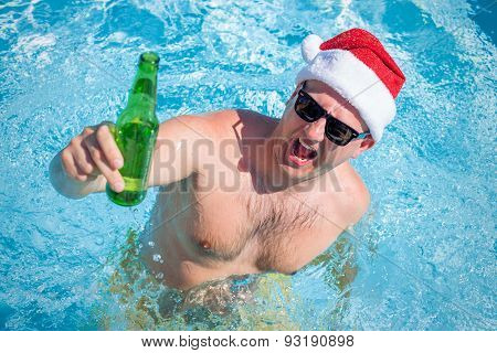 Man with santa hat partying in swimming pool with beer bottle in hand