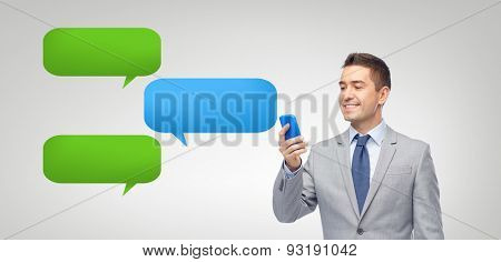 business, people, communication and technology concept - happy businessman texting or reading message on smartphone over messenger text bubbles and gray background