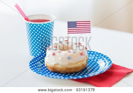 american independence day, celebration, patriotism and holidays concept - close up of glazed sweet donut decorated with flag and juice in disposable tableware at 4th july party