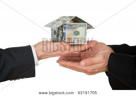 Businessman's Hand Holding House Made Of American Dollar