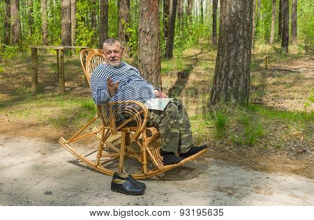 Senior man is having rest in coniferous forest