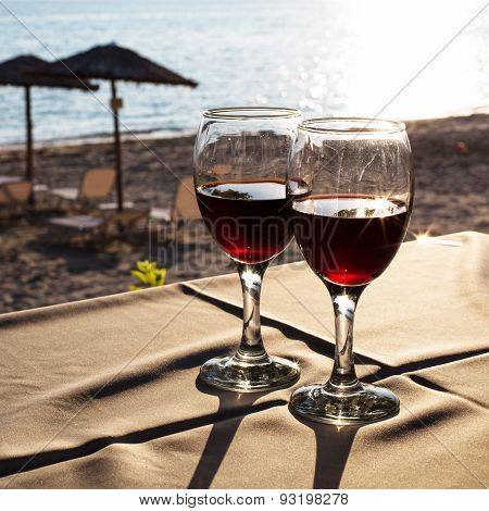 Two Glasses With Red Wine And Sunset On Beach  At The Background