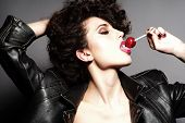 stock photo of licking  - Passionate young girl with curly hair in black leather jacket licking round red lollipop touching hair standing on grey background horizontal picture - JPG