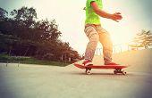 picture of skateboard  - skateboarder legs riding skateboard at skatepark - JPG