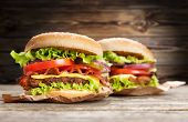 stock photo of hamburger-steak  - Delicious hamburger and fries on wooden background - JPG