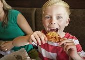 picture of take out pizza  - Cute little boy taking a big bite of cheese pizza at a restaurant - JPG