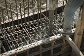 pic of concrete pouring  - Building construction worker pouring cement or concrete with pump tube - JPG