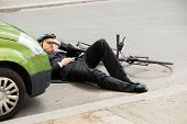 pic of accident victim  - Unconscious Male Cyclist Lying On Road After Road Accident - JPG