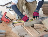 image of home addition  - Carpenter man measuring plank of wood for Home Building - JPG