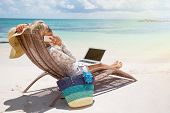 picture of productivity  - Young productive businesswoman working on the beach - JPG