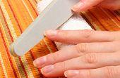 stock photo of nails  - Woman with file filing nails woman polishing nails manicure nail care - JPG