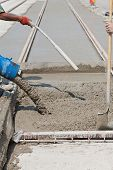 foto of concrete pouring  - construction team pouring concrete on a road with boots and protection gear - JPG