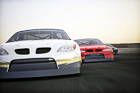 pic of race track  - Front view of auto racing race cars racing on a track with motion blur - JPG