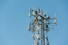 pic of antenna  - Top part of cell phone communication tower with multiple antennas against a blue sky - JPG