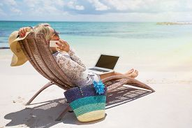 stock photo of productivity  - Young productive businesswoman working on the beach - JPG