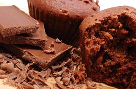 foto of chocolate muffin  - Delicious fresh baked chocolate muffins grated chocolate and portion of chocolate lying on wooden cutting board - JPG