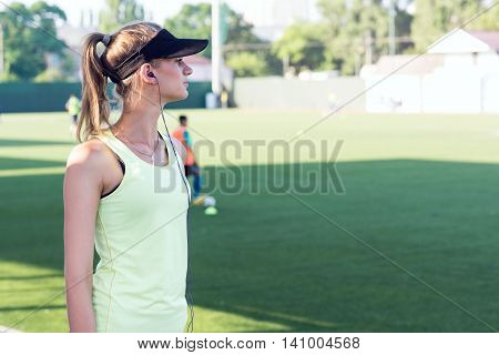 Sporty girl on the stadium. Football stadium. Slim sporty fitness woman. Bottle Shaker protein. Social media and fitness concept. Toned image.