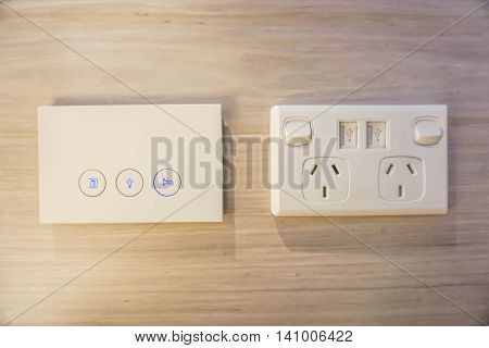 Modern and luxury light switch and plug socket on the wooden wall in the bedroom