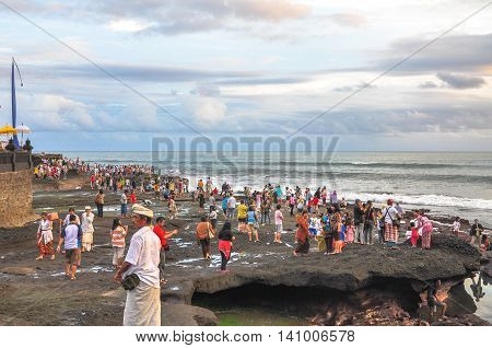 Bali,Indonesia-May 28,2010:People enjoying a view at Tanah Lot,Bali,Indonesia.Tanah Lot is the rock formation off the Indonesian island of Bali & home to the pilgrimage temple Pura Tanah Lot.